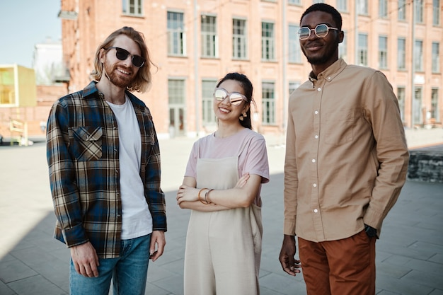 Diverse groep van drie jonge mensen die naar de camera kijken terwijl ze buiten in de stad staan, allemaal met een zonnebril