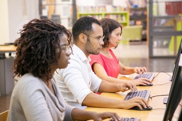 Diverse groep volwassen studenten die in computerklasse werken