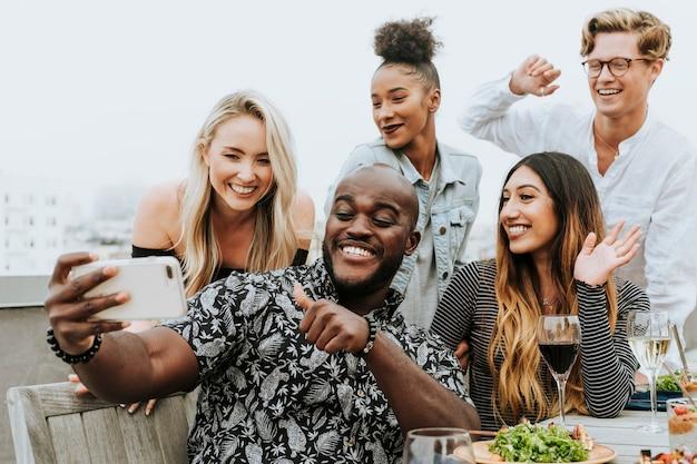 Diverse groep vrienden die een selfie nemen bij een dakpartij