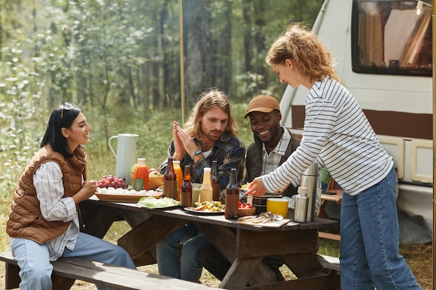 Diverse groep vrienden genieten van picknick buiten op de camping met aanhangwagen