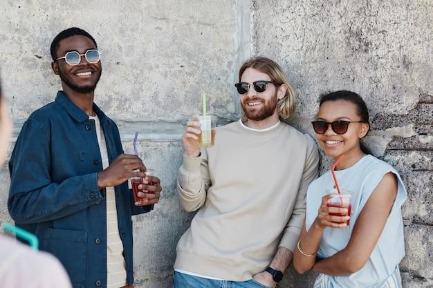 Diverse groep vrolijke jonge mensen die buiten van cocktails genieten in de stedelijke omgeving, kopieer ruimte
