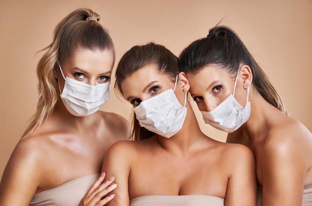 Diverse groep vrouwen die beschermende maskers dragen die over achtergrond worden geïsoleerd