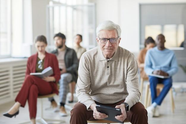 Diverse groep zakenmensen zittend op stoelen in kantoor, focus op moderne senior man die naar camera kijkt