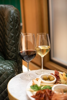 Diverse hapjes. kaasvoorgerecht, vleeswaren, olijven met twee glazen rode en witte wijn in restaurant of café.
