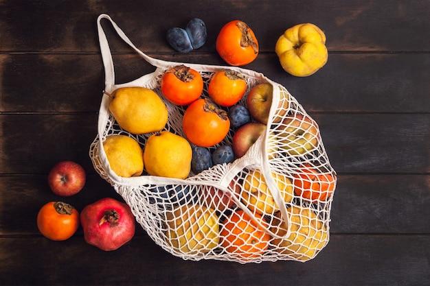 Diverse herfstvruchten in een netzak op een donkere houten achtergrond.