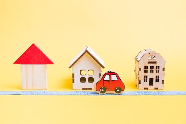 Diverse houten modellen van huizen op een gele achtergrond