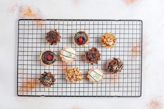 Diverse huisgemaakte minitaartjes met noten en chocoladeroom.
