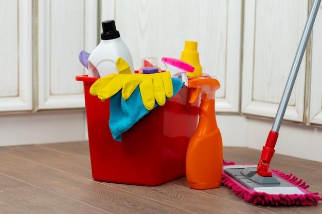 Diverse huishoudelijke schoonmaakmiddelen en flessen in een plastic emmer op de vloer
