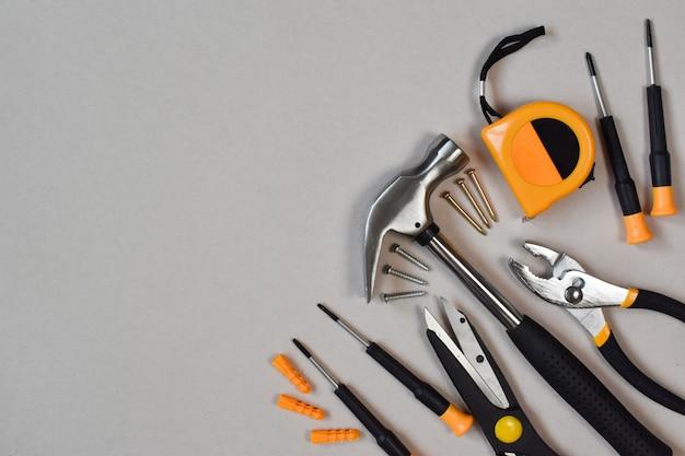 Diverse hulpmiddelen van de bouw met handgereedschap voor huisreparatie en onderhoud op een witte achtergrond.