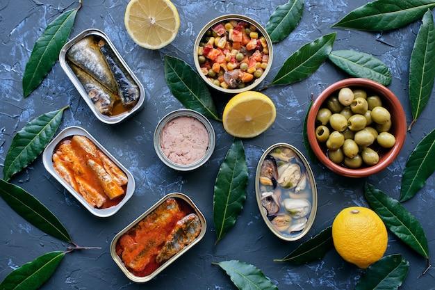 Diverse ingeblikte groenten en vis in blikjes. op een gestructureerde stenen achtergrond