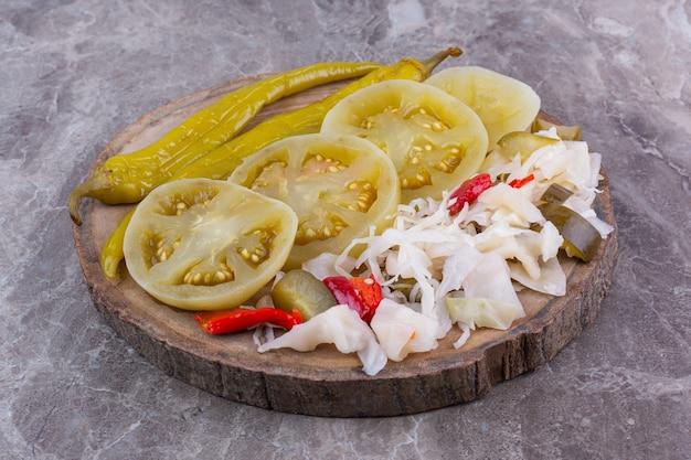 Diverse ingeblikte groenten op een bord, op het marmer.
