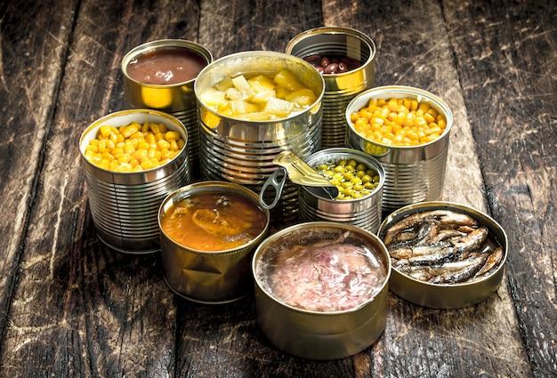 Diverse ingeblikte groenten, vlees, vis en fruit in blikjes op houten tafel.