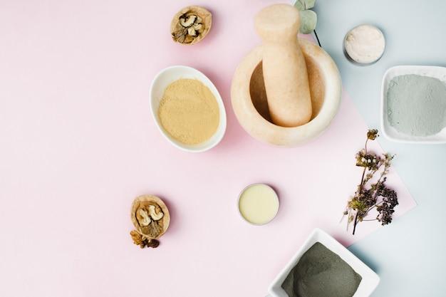 Diverse ingrediënten voor de huidverzorging thuis. marmermortel voor het mengen van klei, eucalyptusplaten, walnoten om een balsem of crème te verkrijgen. hydrateert en reinigt de huid