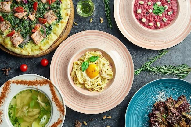 Diverse italiaanse gerechten op een donkere ondergrond: carbonara-pasta, zalmpizza, risotto van rode biet, zelfgemaakte kippenbouillon en salade. bovenaanzicht plat voedsel