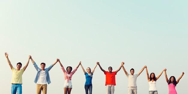 Diverse jonge mensen hand in hand