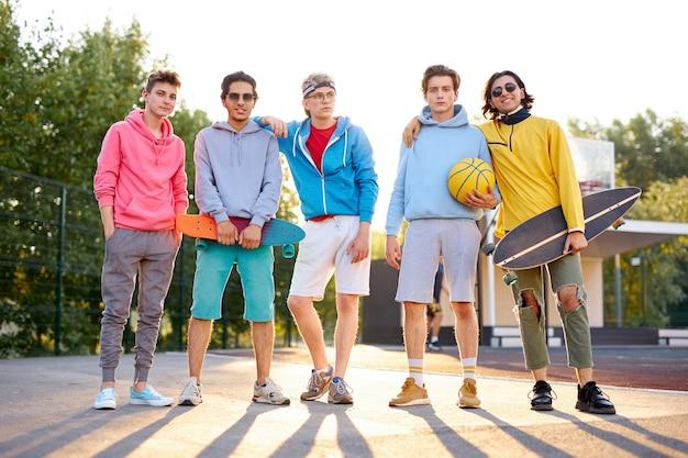 Diverse jonge stadsjongens staan klaar om samen te basketballen