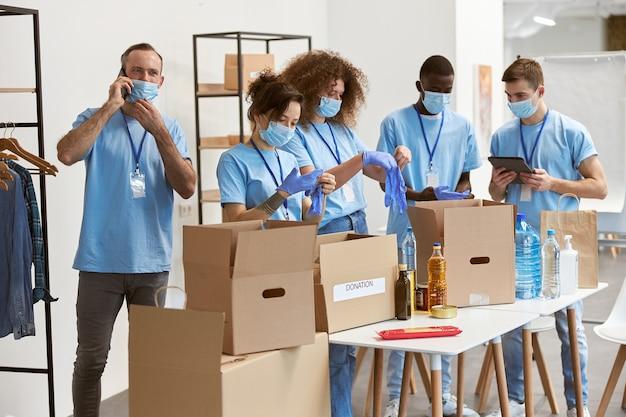 Diverse jonge vrijwilligers met beschermende maskers die handschoenen aantrekken voor het sorteren van het verpakken van voedsel in