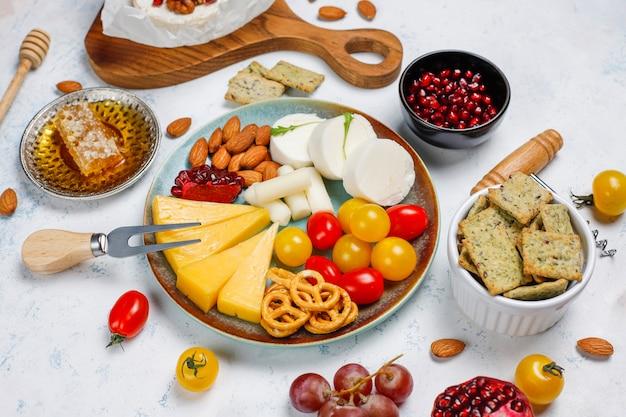 Diverse kaas en kaasplaat op lichte tafel met verschillende noten en fruit