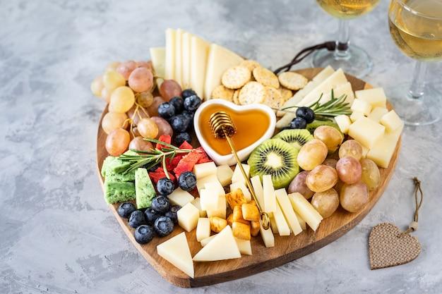Diverse kazen op een houten snijplank in de vorm van een hart. kaas, druiven, walnoten, olijven, rozemarijn en een glas witte wijn.