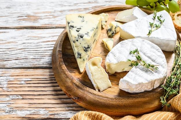 Diverse kazen op een ronde houten snijplank. camembert, brie en blauwe kaas met druiven. witte houten achtergrond. bovenaanzicht. kopieer ruimte.