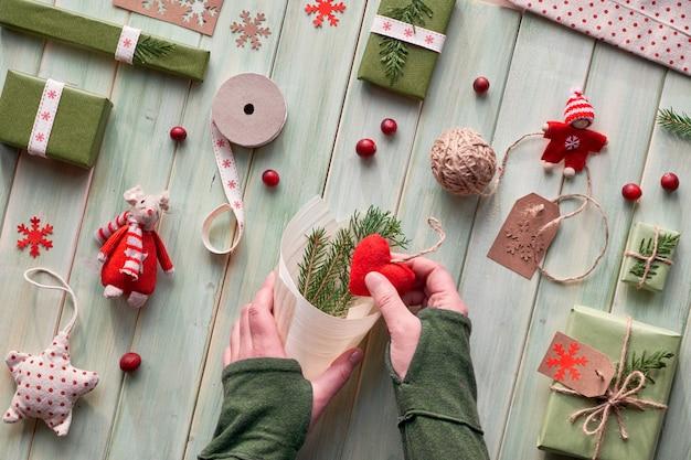 Diverse kerst- of nieuwjaarswintervakantie eco-vriendelijke decoraties, ambachtelijke papieren verpakkingen en herbruikbare of afvalvrije geschenken. plat lag op hout, handen decoreren triplex kegel met groene bladeren.