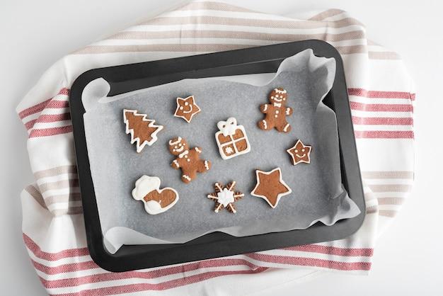 Diverse kerstkoekjes met geglazuurde suikersuikerglazuur op bakplaat. traditioneel bakken.
