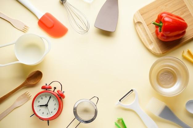 Diverse keukengerei met een groente op een beige achtergrond, met plaats voor tekst. plat liggen.