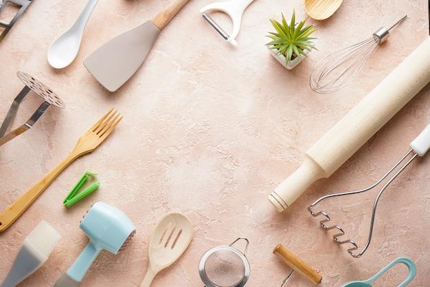 Diverse keukengerei op een beige achtergrond, met plaats voor tekst. plat liggen.
