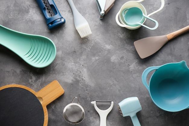 Diverse keukengerei op grijze tafel, met plaats voor tekst. plat liggen.
