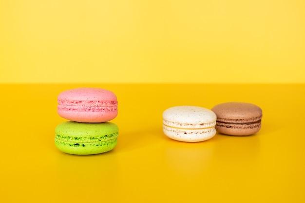 Diverse kleurrijke bitterkoekjes op gele achtergrond