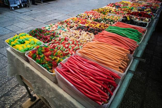Diverse kleurrijke gelei-snoepjes en snoepgoed tentoongesteld in plastic dozen te koop op straat. contrasterende kleuren van snoep en zoete potloden die te koop worden aangeboden voor straatshoppers. aantrekkelijkheid voor kinderen.