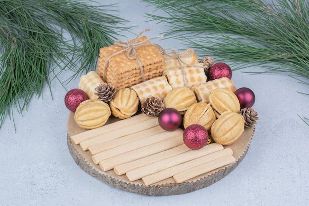Diverse koekjes en kerstversieringen op een houten bord.