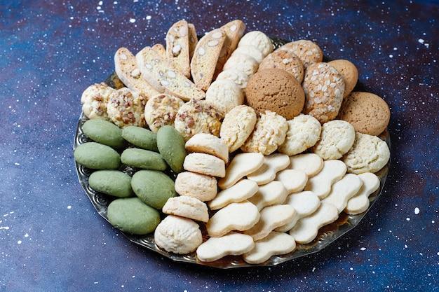 Diverse koekjes in een houten dienblad op grijs