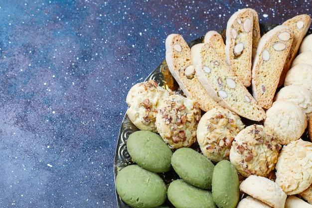 Diverse koekjes in een houten dienblad op grijze achtergrond