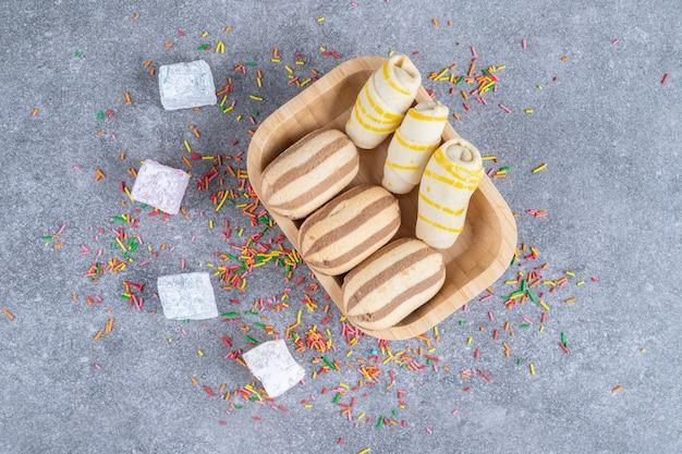 Diverse koekjes op houten plaat met snoepjes en hagelslag