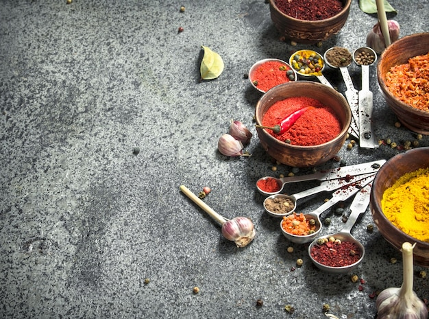 Diverse kruiden en specerijen met maatlepels op rustieke tafel.