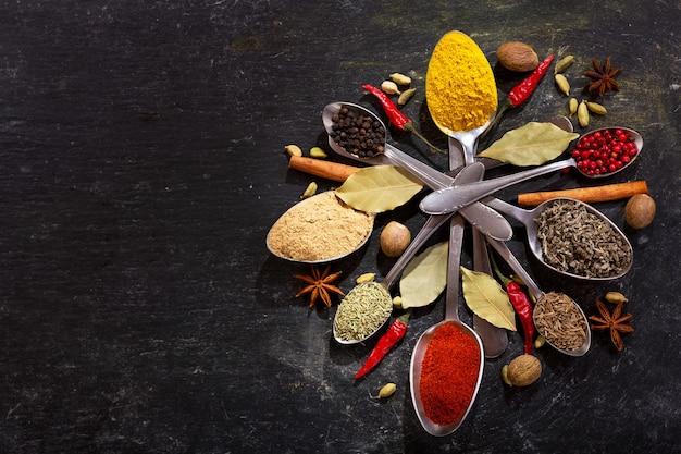 Diverse kruiden en specerijen voor het koken op een donkere, bovenaanzicht