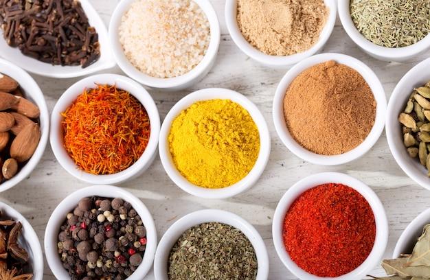 Diverse kruiden en specerijen voor het koken op een houten tafel, bovenaanzicht