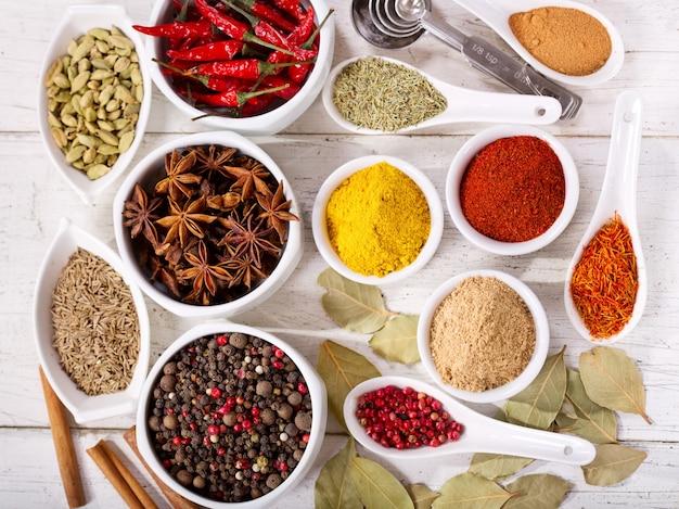 Diverse kruiden en specerijen voor het koken op houten tafel, bovenaanzicht