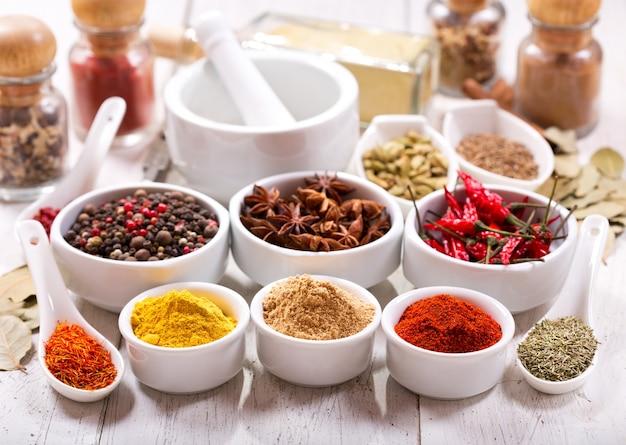 Diverse kruiden en specerijen voor het koken op houten tafel