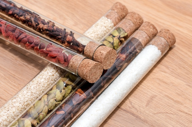 Diverse kruiden in glazen flessen op een houten keukentafel.