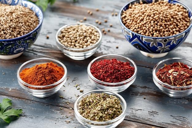 Diverse kruiden in kommen op grijze tafel. paprika, kurkuma, rode peper, komijn, koriander. kruidenpoeder