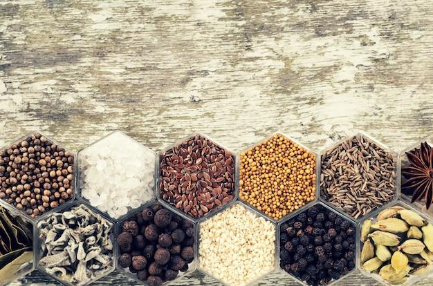 Diverse kruiden in zeshoekige potten op een houten ondergrond