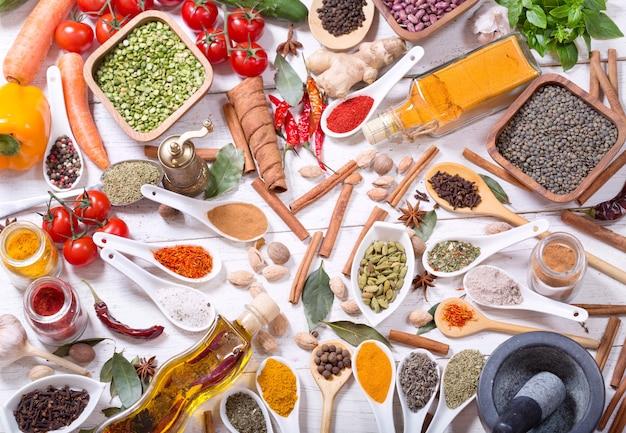 Diverse kruiden, specerijen en groenten voor het koken op houten tafel, bovenaanzicht