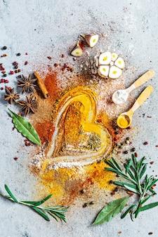 Diverse kruidenpoeders paprika kerrie koriander gember gedroogde uien en knoflook kurkuma kaneel peper anijs en kruiden op grijze achtergrond indiase en aziatische keuken liefde voor specerijen