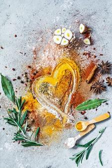 Diverse kruidenpoeders paprika kerrie koriander gember gedroogde uien en knoflook kurkuma kaneel peper anijs en kruiden rozemarijn laurier op grijze achtergrond indiase en aziatische keuken