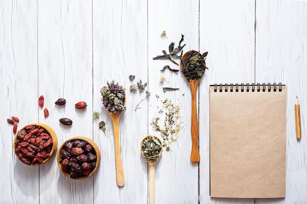 Diverse kruidenthee, rozenbottels, gojibessen en een blanco notitieblok op een witte houten tafel