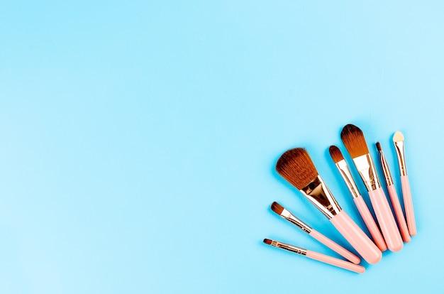 Diverse make-up borstels roze set met leeg frame voor tekst op blauw papier