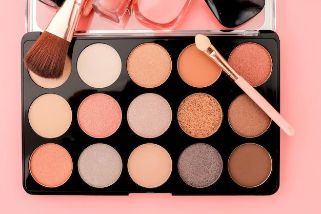 Diverse make-up productson roze achtergrond met copyspace.
