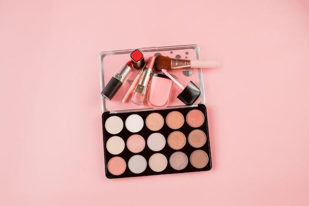 Diverse make-upproducten op roze achtergrond met copyspace